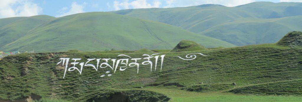 Karmapa Khyeno made from white rocks on the hillside near the entrance to Begun Monastery