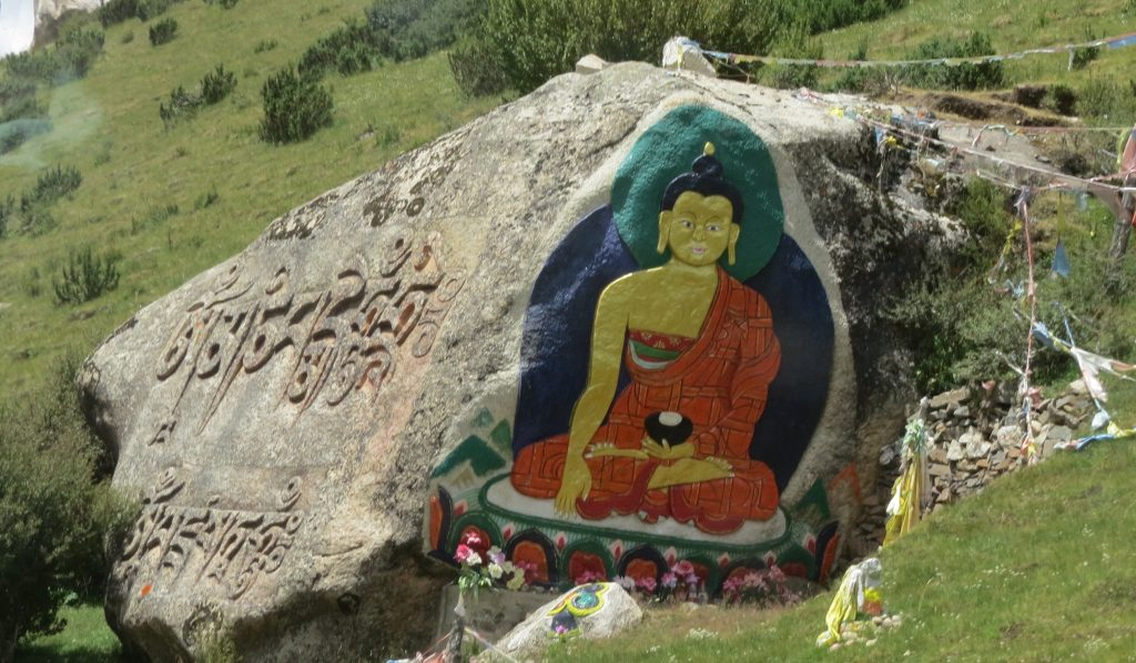 Painted rocks and carved mantras along the road.